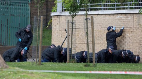 Police search for evidence near the scene of the killing. Photograph: Neil Hall/Reuters
