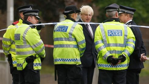 Mayor of London Boris Johnson confers with police officers near the scene of the soldier's killing. Photograph: Luke MacGregor/Reuters