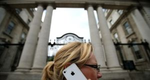 A woman on her Apple iPhone outside Government Buildings in Dublin yesterday. Photograph: Julien Behal/PA Wire