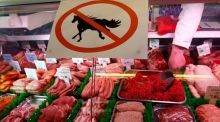 "A butcher  works behind a ""no horsemeat"" sign  in Market Harborough, central England. Photograph: Reuters"