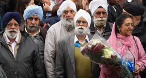 Members of the Sikh community wait to lay flowers yesterday close to the crime scene in Woolwich, London, where 25-year-old soldier Lee Rigby was murdered on Wednesday. Photograph: Dan Kitwood/Getty Images
