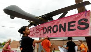 "A demonstrator adjusts a sign reading ""Stop Killer Drones"" hung on a mock drone at the gates of Fort McNair where US president Barack Obama spoke yesterday. Photograph: Kevin Lamarque/Reuters"