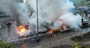 Firemen extinguish a row of burning cars in the Stockholm  suburb of Rinkeby after youths rioted in several different suburbs around the Swedish capital. Photograph: Fredrik Sandberg/Scanpix/Reuters