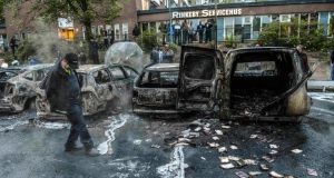 A bystander checks the debris around a row of burnt cars in the Stockholm suburb of Rinkeby. Photograph: Fredrik Sandberg/Scanpix/Reuters