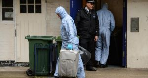 Police forensics officers remove evidence from a flat at Macey House, in Greenwich, southeast London, yesterday. Photograph: Dominic Lipinski/PA Wire