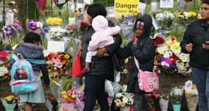 Members of the community look at floral tributes close to the scene where Drummer Lee Rigby of the 2nd Battalion the Royal Regiment of Fusiliers was killed. Photograph: Dan Kitwood/Getty Images