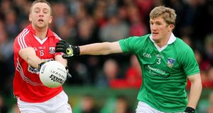 Limerick's Johnny McCarthy tries to dispossess Paul Kerrigan  Cork) during the Munster Senior Football Championship quarter-final at the  Gaelic Grounds. Photograph: Cathal Noonan/Inpho