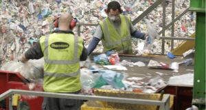 Sorting through mixed dry recyclables at Park West Business Park, Dublin 12. People have to be employed to remove contaminants, an added cost for waste companies. Photograph: Dara Mac Dónaill
