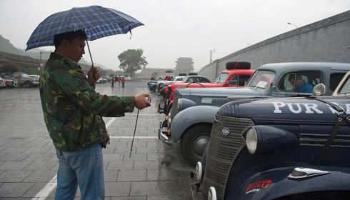 A Chinese fan takes photos of fancy old motors, about to dash off to Paris. Photograph: China Daily/Reuters
