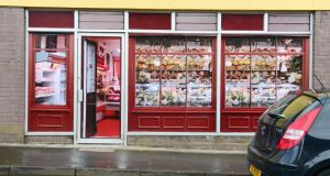 Stickers applied to the windows of a former butcher's shop in Belcoo, Co Fermanagh, give the premises the superficial appearance of a thriving business.  Photograph: Bryan O'Brien