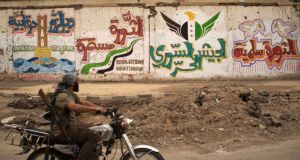A Free Syrian Army fighter rides  past revolutionary graffiti  in Deir al-Zor.