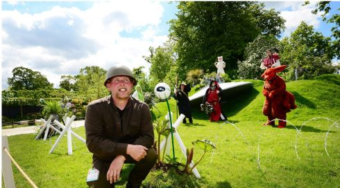 "Fiann O'Nuallain, designer of the Destination Bloom show garden, which features a crashed flying saucer (at back) and draws attention to the dangers of invasive plants. Here he is joined by ""cosplayers"", also known as role-players, offering some science fiction-related fun. Photograph: Bryan O'Brien/The Irish Times"