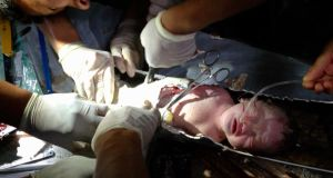 Rescued: firefighters and doctors carefully snip Baby 59 from the toilet pipe. Photograph: Reuters