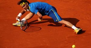 Fabio Fognini of Italy stretches to play a forehand against Rafael Nadal of Spain on day seven of the French Open at Roland Garros in Paris. Photograph:  Clive Brunskill/Getty Images