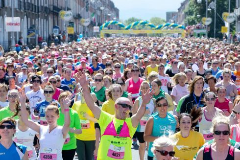 Happy competitors take off from the start line in a sunny city centre.  Photograph: Inpho/Morgan Treacy