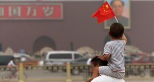 A boy holds a Chinese national flag as he sits on the shoulders of a man in front of a portrait of   Mao Zedong at Tiananmen Square in Beijing this week.  Photograph:  Kim Kyung-Hoon/Reuters