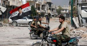 Forces loyal to Syrian president Bashar al-Assad carry the national flag as they ride on motorcycles in Qusayr, after the Syrian army took control from rebel fighters yesterday.  Photograph: Reuters/Mohammed Azakir