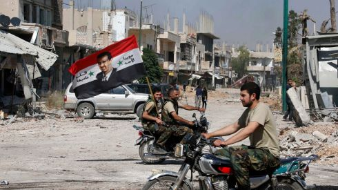 Forces loyal to Syria's president Bashar al-Assad carry the national flag as they ride on motorcycles in Qusayr, after the Syrian army took control from rebel fighters. Photograph: Mohammed Azakir/Reuters
