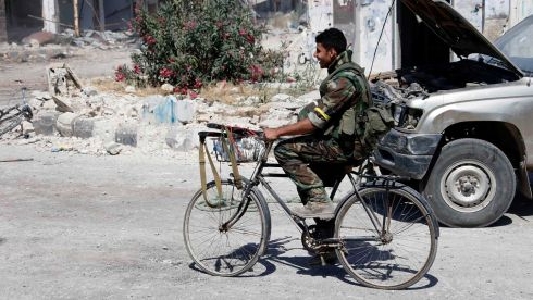 A soldier loyal to the Syrian regime rides a bicycle in Qusayr, after the Syrian army took control of the city from rebel fighters. Photograph: Mohamed Azakir/Reuters