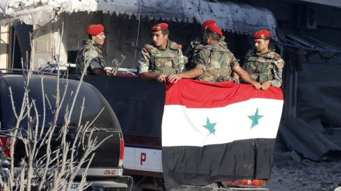 "Soldiers loyal to the Syrian regime stand in a truck in Qusayr. The Syrian military command declared, ""We will not hesitate to crush with an iron fist those who attack us. Their fate is surrender or death. We will continue our string of victories until we regain every inch of Syrian soil.""  Photograph: Mohamed Azakir/Reuters."