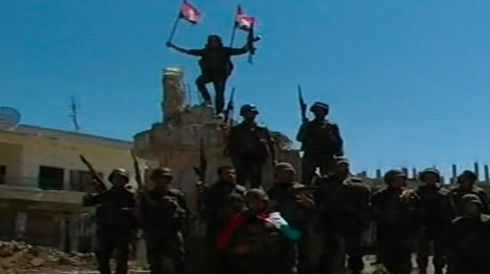 The fall of Qusayr was symbolised by televised images of a soldier planting a Syrian flag on the bullet-riddled clock tower in the town centre, among heavily damaged buildings and rubble. Photograph: Syrian Tv/Handout via Reuters