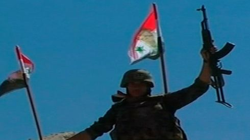 A soldier raises his weapon while holding a Syrian flag. Photograph: Syrian Tv/Handout via Reuters