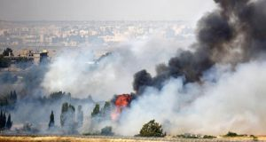 Smoke rises as a fire burns near the Kuneitra border crossing, as seen from the Israeli occupied Golan Heights, close to the ceasefire line between Israel and Syria. Photograph: Ammar Awad/Reuters