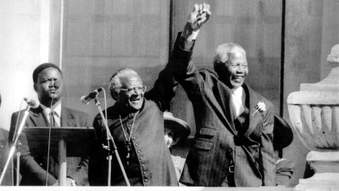 Archbishop Desmond Tutu joins hands with Nelson Mandela in triumph after the latter was proclaimed president of South Africa in 1994.