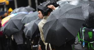 Job applicants wait in line under rainfall in New York.