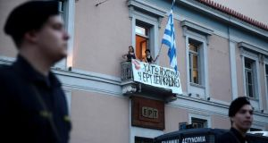 An employee stands at a balcony of the studio of state broadcaster ERT in Athens yesterday. Photograph: Reuters.