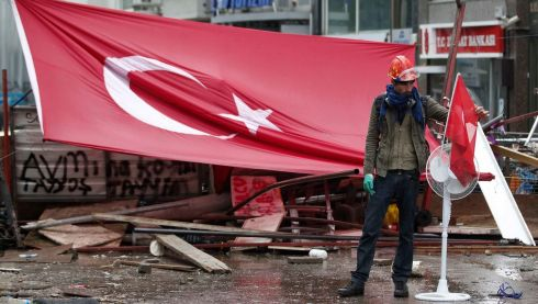 A protester fixes a Turkish flag to a fan in front of a barricade in Istanbul's Taksim Square today.  Photograph: Osman Orsal/Reuters
