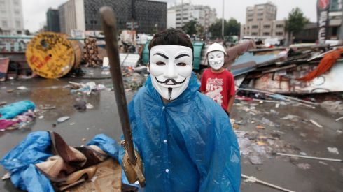 A boy wearing a Guy Fawkes mask displays his wooden sword behind a barricade at Gezi Park in central Istanbul today.  Photograph: Osman Orsal/Turkey
