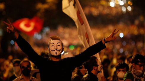 An anti-government protester, wearing a Guy Fawkes mask, makes V-signs in front of a barricade during clashes in Ankara.  Photograph: Umit Bektas/Reuters