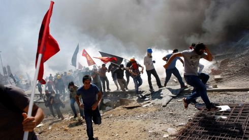 Protesters run as riot police fire teargas. Photograph: Murad Sezer/Reuters
