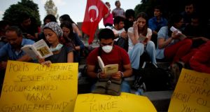 Anti-government protesters read books at Kizilay Square in Ankara yesterday. They gathered for the reading in an attempt to circumvent police bans against mass gatherings and protests in the capital. Photographj: Dado Ruvic/Reuters