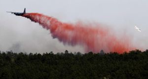 An airplane drops flame retardant over the Black Forest Fire north of Colorado Springs, Colorado, yesterday.  The fire has reportedly burned 80 to 100 homes and has charred at least 8,000 acres. Photograph: Chris Schneider/Getty Images