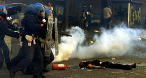 Violent clashes: police storm past the body of a protester who was shot and killed by carabinieri during rioting at a G8 summit in Genoa in July 2001. Photogaph: Dylan Martinez/Reuters