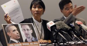 Pro-democracy lawmaker Claudia Mo holds a letter to US president Barack Obama, beside a combination photo featuring Obama and Edward Snowden, at a news conference in Hong Kong yesterday in support of Snowden. Photograph: Bobby Yip/Reuters