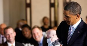US president Barack Obama holds a guest's baby during a Father's Day luncheon in the  White House yesterday. The president is to address a youthful audience in the North about prospects for the region during his visit for the G8 summit. Photograph: Christopher Gregory/the New York Times