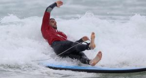 Conor Murray of the British & Irish Lions, falls off the surfboard during surfing lessons on Bondi Beach.