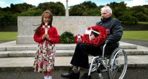 Zowie Brown, aged six, whose great grandfather was a pardoned Irish soldier, attends a wreath-laying ceremony  at the  National War Memorial in Islandbridge, Dublin, with second World War  veteran  Phillip Farrington. Photograph: Julien Behal/PA Wire