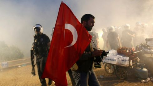 A protester holds a Turkish flag as riot police order them to evacuate Gezi Park in central Istanbul. Photograph: Murad Sezer/Reuters