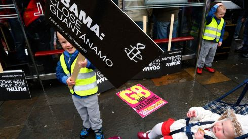A boy holds a placard during the  protest in Belfast.  Photograph: Yves Herman/Reuters