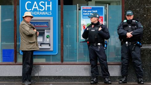 Police officers keep guard outside of a bank in Belfast. Photograph: Yves Herman/Reuters