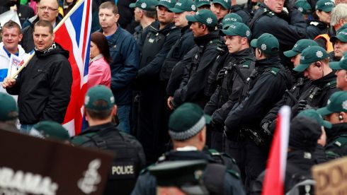 Riot police stand guard over a loyalist protester holding a Union flag near  an anti-G8 demonstration in Belfast. Photograph: Cathal McNaughton/Reuters