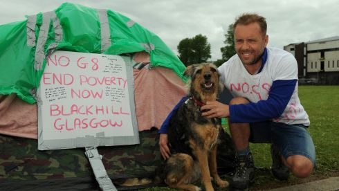 G8 protester Andrew Carnegie (43) from Glasgow with his dog Grace at their makeshift camp at Broadmeadow in Enniskillen. Photograph: Joe Giddens/PA Wire
