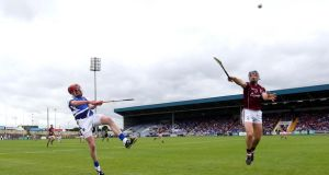 Zane Keenan of Laois gets his shot away under pressure from Galway's Shane Kavanagh. Photograph: Donall Farmer/Inpho
