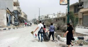 Residents of Qusayr carry bags after visiting their houses to collect belongings. Photograph: Reuters/Rami Bleibel