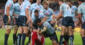 Jonny Sexton of the Lions is surounded by  Waratahs players . Photoraph: Mark Kolbe/Getty Images