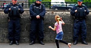 A girl waves towards police officers in Enniskillen, Co Fermanagh yesterday. A large security operation is in place around Enniskillen and Lough Erne ahead of the G8 summit, which begins today. Photograph: Yves Herman/Reuters